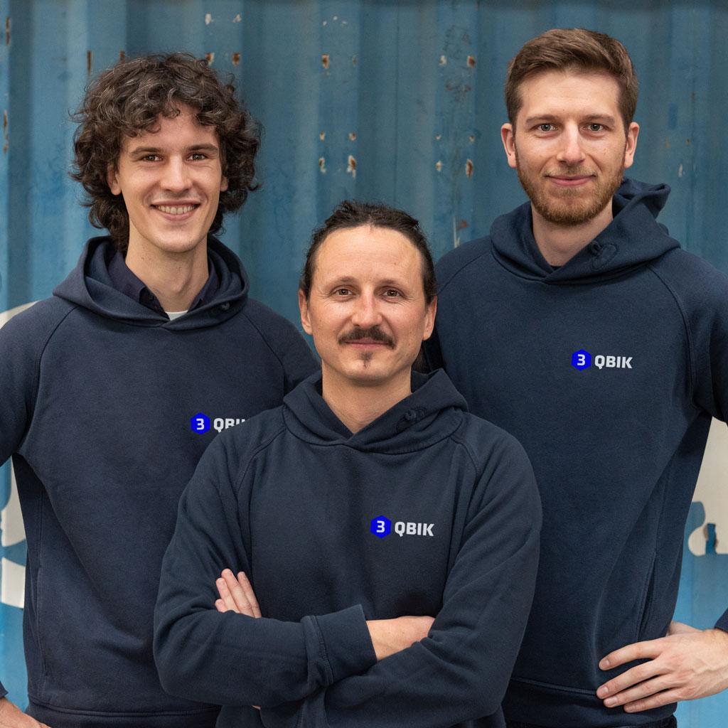 Teamfoto von den WordPress Experten vor einem Schiffscontainer: Moritz Bappert, Lennart Schleifer und Joscha Holzhäuer